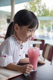 Asian little Chinese girl drinking juice Royalty Free Stock Images