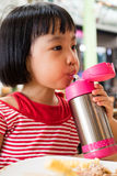 Asian Little Chinese Girl Drinking Water from Stainless Steel Bo. Ttle in Outdoor Cafe Stock Image