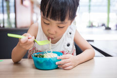 Asian little Chinese girl eating beef noodles. In outdoor cafe Royalty Free Stock Images