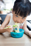 Asian little Chinese girl eating beef noodles. In outdoor cafe Royalty Free Stock Photo