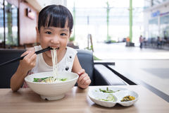 Asian little Chinese girl eating beef noodles soup. In outdoor cafe stock image