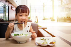 Asian little Chinese girl eating beef noodles soup. In outdoor cafe royalty free stock photos