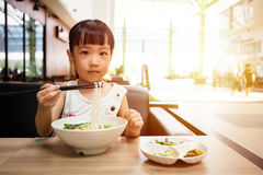 Asian little Chinese girl eating beef noodles soup. In outdoor cafe royalty free stock photo