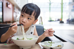 Asian little Chinese girl eating beef noodles soup Stock Image