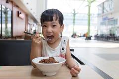 Asian little Chinese girl eating braised pork rice Stock Image