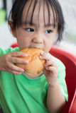 Asian little Chinese girl eating bread Royalty Free Stock Image
