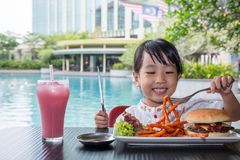 Asian Little Chinese Girl Eating Burger and French fries. At Outdoor Cafe Royalty Free Stock Photos