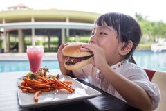 Asian Little Chinese Girl Eating Burger and French fries. At Outdoor Cafe Stock Images