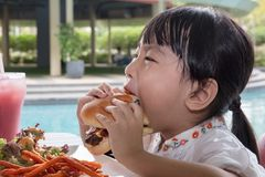 Asian Little Chinese Girl Eating Burger and French fries. At Outdoor Cafe Royalty Free Stock Photography