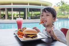 Asian Little Chinese Girl Eating Burger and French fries. At Outdoor Cafe Stock Photography
