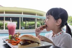 Asian Little Chinese Girl Eating Burger and Fried chicken. At Outdoor Cafe Stock Photography
