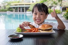 Asian Little Chinese Girl Eating Burger and Fried chicken. At Outdoor Cafe Stock Images