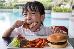 Asian Little Chinese Girl Eating Burger and Fried chicken. At Outdoor Cafe Royalty Free Stock Images