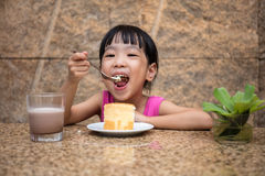Asian little Chinese girl eating delicious cake Royalty Free Stock Photography