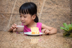 Asian little Chinese girl eating delicious cake Royalty Free Stock Image