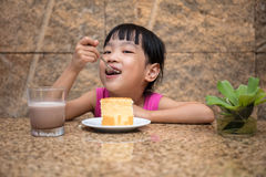 Asian little Chinese girl eating delicious cake Stock Photo