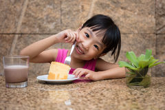 Asian little Chinese girl eating delicious cake Royalty Free Stock Photos
