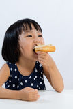 Asian Little Chinese Girl Eating Donuts Royalty Free Stock Photos