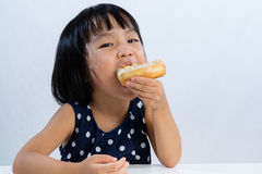 Asian Little Chinese Girl Eating Donuts Royalty Free Stock Photo