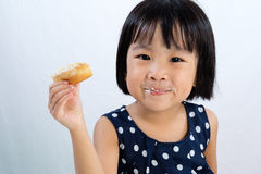 Asian Little Chinese Girl Eating Donuts Stock Images