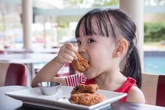 Asian Little Chinese Girl Eating Fried chicken Royalty Free Stock Images