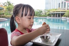 Asian Little Chinese Girl Eating Fried chicken. At Outdoor Cafe Stock Image