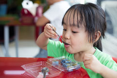 Asian little Chinese girl eating glutinous rice Stock Image