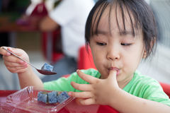 Asian little Chinese girl eating glutinous rice Royalty Free Stock Photo