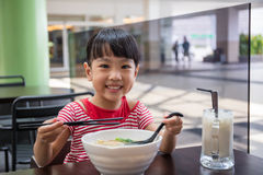 Asian little Chinese girl eating noodles soup. In outdoor cafe Stock Photo