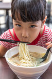 Asian little Chinese girl eating noodles soup. In outdoor cafe Royalty Free Stock Photography