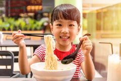 Asian little Chinese girl eating noodles soup. In outdoor cafe Stock Images