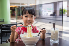 Asian little Chinese girl eating noodles soup Stock Image