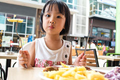 Asian Little Chinese Girl Eating Western Food Royalty Free Stock Photos