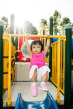 Asian little Chinese girl hanging on horizontal monkey bar. At the playground during the summer time Stock Photo