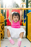 Asian little Chinese girl hanging on horizontal monkey bar. At the playground during the summer time Stock Image