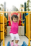 Asian little Chinese girl hanging on horizontal monkey bar. At the playground during the summer time Stock Photography