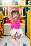 Asian little Chinese girl hanging on horizontal monkey bar. At the playground during the summer time Royalty Free Stock Image