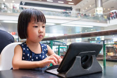 Asian Little Chinese Girl Looking at Digital Tablet Stock Photos