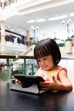 Asian Little Chinese Girl Looking at Digital Tablet Stock Photo