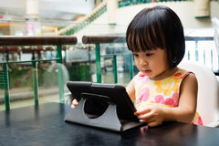 Asian Little Chinese Girl Looking at Digital Tablet Stock Image