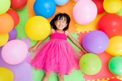 Asian Little Chinese Girl Lying on the Floor amongst Colorful Ba Stock Photo