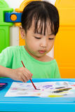 Asian Little Chinese Girl Painting with Brush Stock Photos