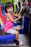 Asian Little Chinese Girl Playing Arcade Game Machine. At a indoor Amusement Playground Stock Photos