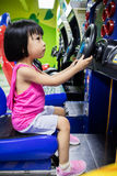 Asian Little Chinese Girl Playing Arcade Game Machine. At a indoor Amusement Playground Stock Photography