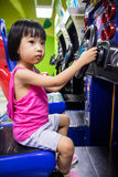 Asian Little Chinese Girl Playing Arcade Game Machine. At a indoor Amusement Playground Stock Image