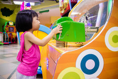 Asian Little Chinese Girl Playing Arcade Game Machine Royalty Free Stock Photos