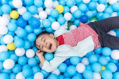 Asian Little Chinese Girl Playing At Balls Pool. In Indoor Playground Royalty Free Stock Photo