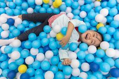 Asian Little Chinese Girl Playing At Balls Pool. In Indoor Playground Royalty Free Stock Images
