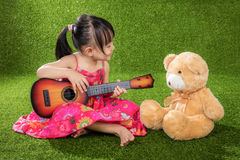 Asian Little Chinese girl playing guitar with teddy bear. Asian Little Chinese girl sitting on grass and playing guitar with teddy bear at outdoor park Stock Photography