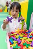 Asian Little Chinese Girl playing puzzle tube. At Indoor Playground Stock Image